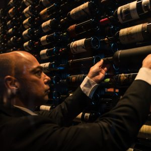 Someone selecting a bottle of wine from 1919's collection.