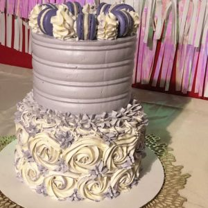 A purple and lavender baby shower cake with purple macarons on top.
