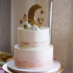 A pink and gold baby shower cake with a moon and stars on top.