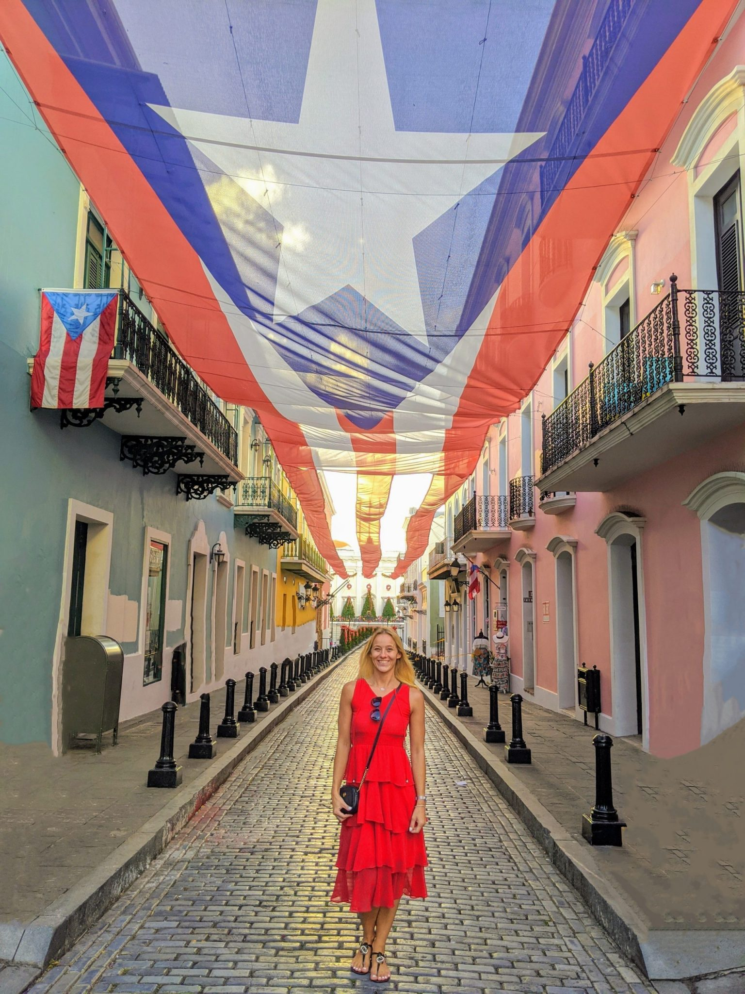 Anna in front of a large Puerto Rican flag hanging above an entire street after her relocation