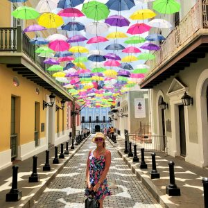 Anna in front of the street covered by bright umbrellas
