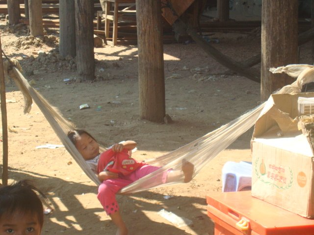A photo of a small girl sleeping in a hammock in Kompong Phluk, Cambodia
