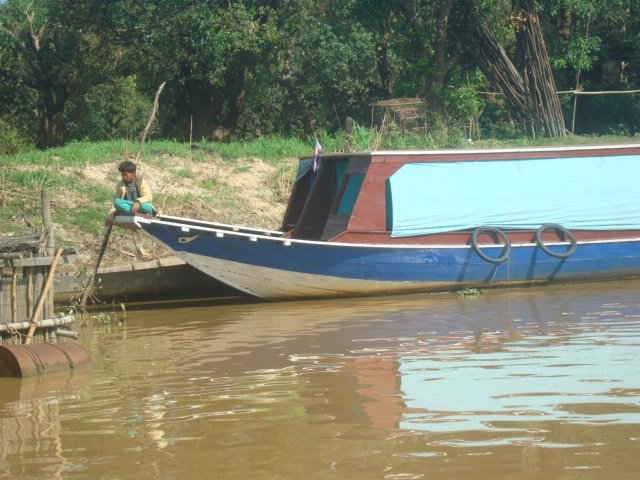 A photo of a child sitting on a medium sized boat