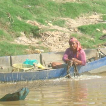 A villager working out of her canoe by the water.