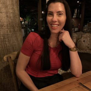 Leesa Truesdell sitting at a table and smiling after living abroad.