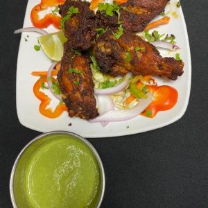 Photo provided by Authentikka. Chicken wings plated on sliced red bell peppers and red and green onions, with a side of green sauce in metro Detroit.