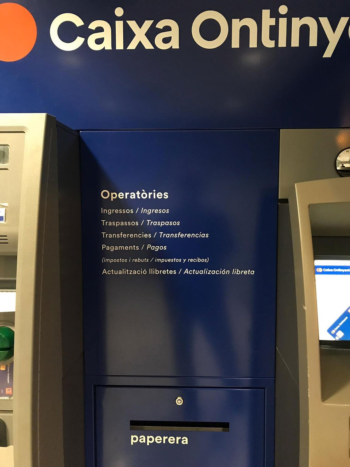Bilingual sign in Ontinyent, Valencia listing different ATM signs