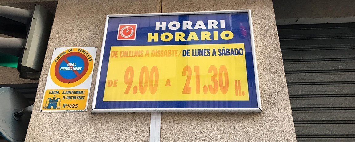 Bilingual sign in Ontinyent, Valencia showing a supermarket's operating hours and day
