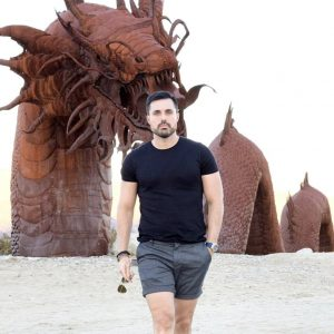 Marcos, hospitality professional, walking on the beach in front of a statue of a sea monster in Borrego Springs, California.