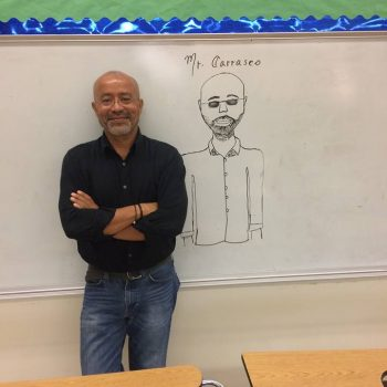 Jose in front of a student-drawn caricature while teaching in Miami