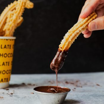 A churro being dipped in chocolate sauce from Chocobar Cortes.