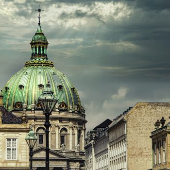 A photo of a building with a green domed roof in Copenhagen, one of the best places to visit in the summer.