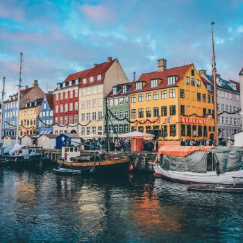 Boats on the canal in front of a row of colorful buildings in Copenhagen, one of the best places to visit in the summer.