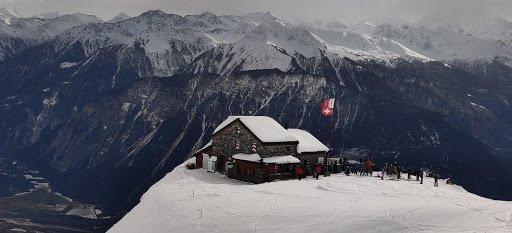 A small restaurant sitting near a snowy mountain cliff.