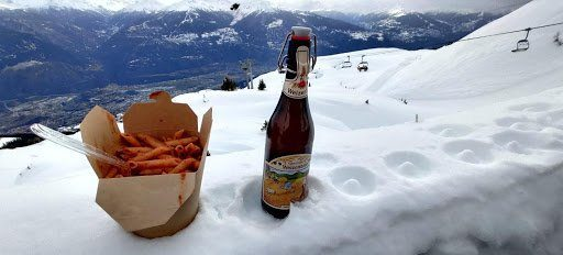 A takeout container of pasta and a bottle of beer in the snow, with a valley in the background.
