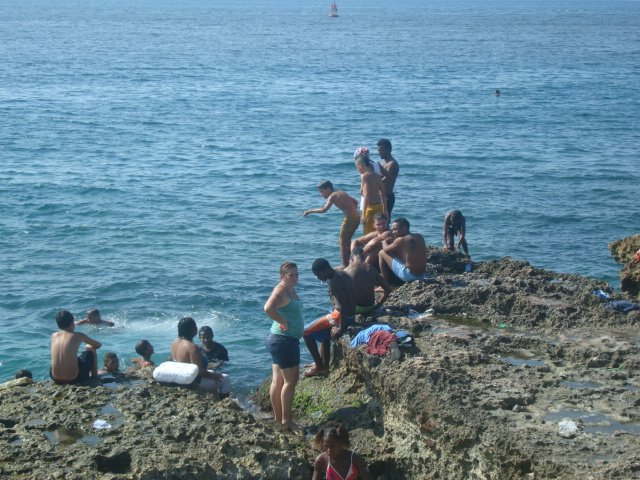 Kids swimming from the rocks by the Malecon