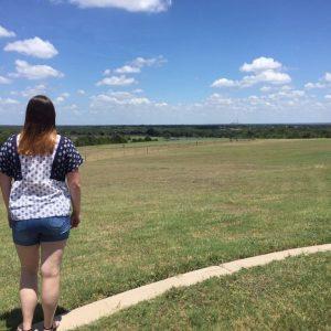 Emma looking across an empty field.