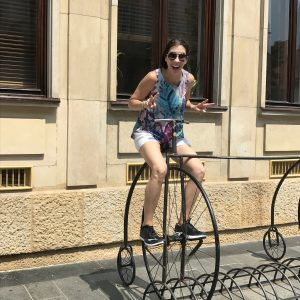 Leesa pretending to ride an old bicycle with a giant front wheel in Europe.