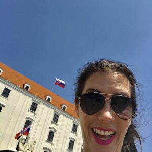 Leesa smiling in front of a large European building.