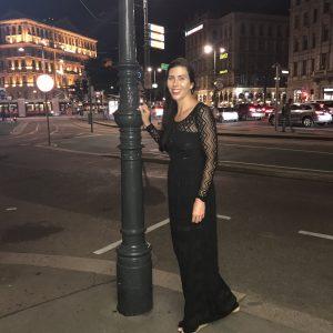 Leesa standing next to a lamp post near the street in an evening dress.