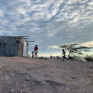 A family running around a gravel road in Haiti