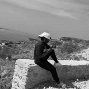 Paunise sitting on a rock in Haiti
