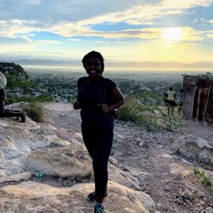 Paunise on a rock in front of a city in Haiti