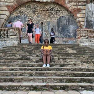 Paunise posing on a large stairway in Haiti.