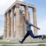 Guy Guyton in front of ancient Greek architecture while traveling abroad, thinking about his travel tips.