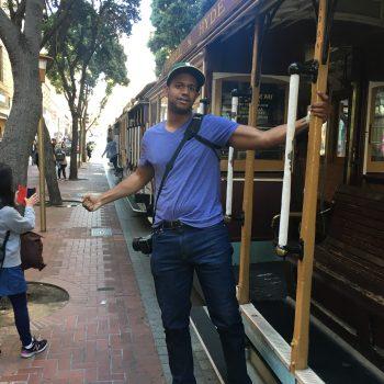 Guy Guyton posing on a trolley in San Francisco