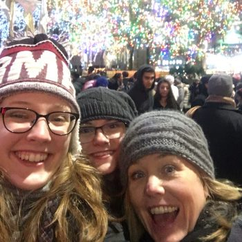 Cassidy, her mom, and her sister posing in front of the Rockefeller Tree on New Year's Eve