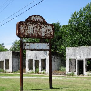 A rusty sign and abandoned buildings.