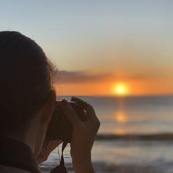 Leesa taking a photo of a beach sunset