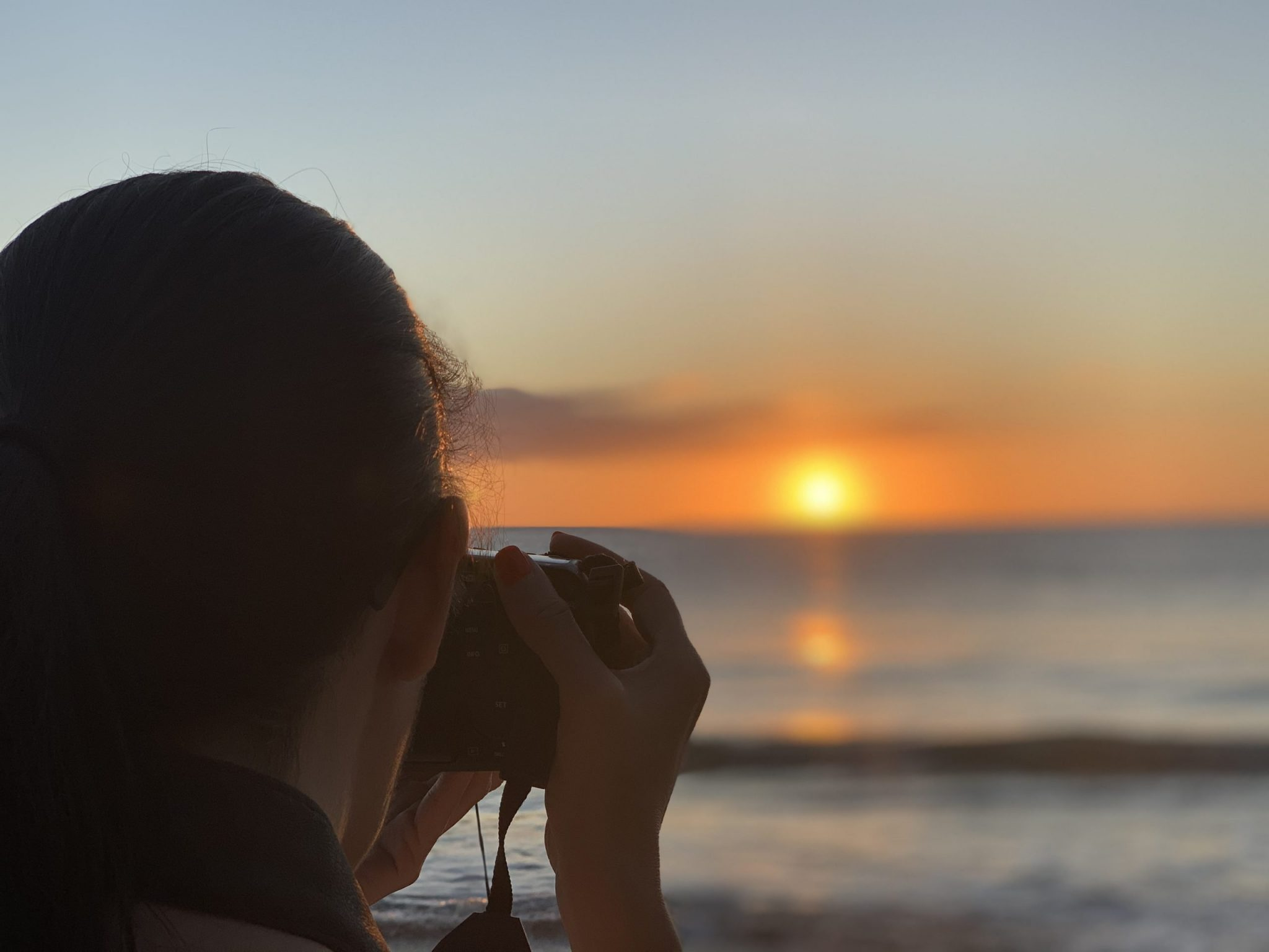 Leesa taking a photo of a beach sunset