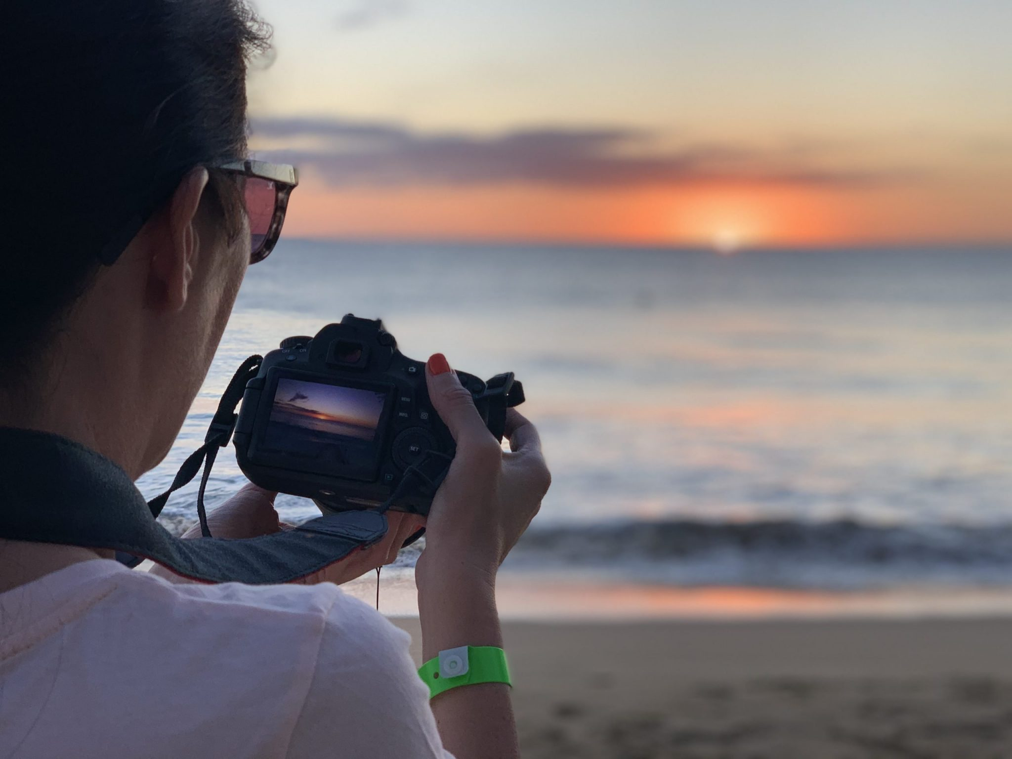 Leesa looking at a picture on a camera while at the beach in early 2020