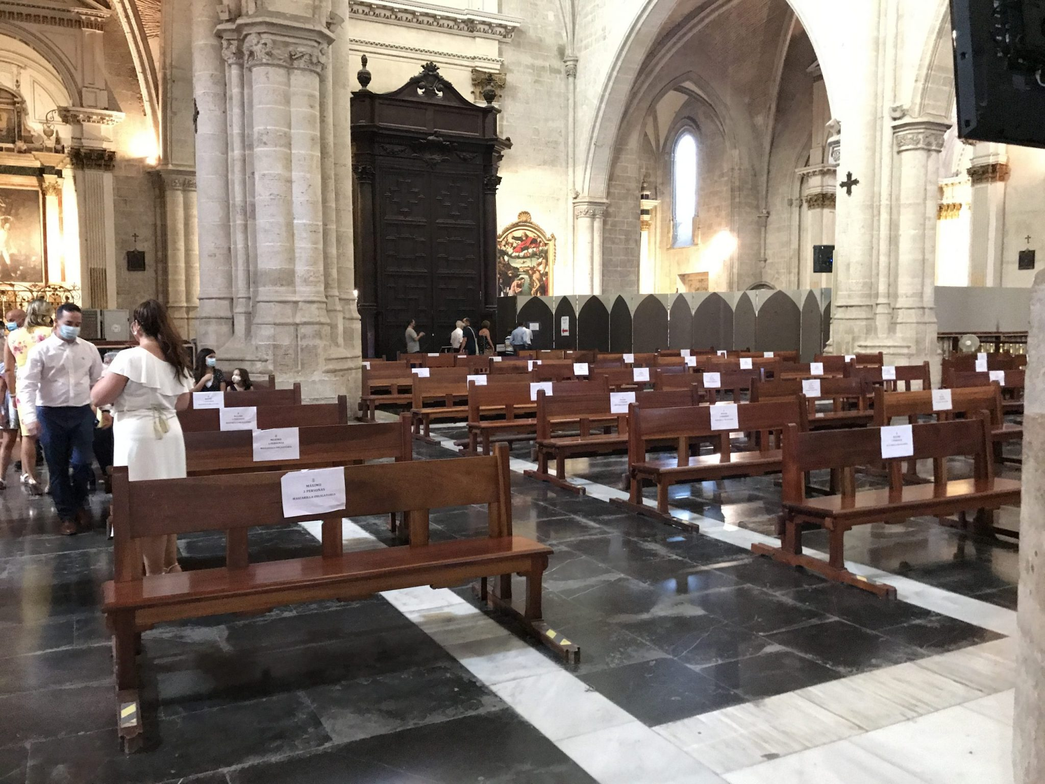An image of church pews with social distancing signs as people start traveling again.