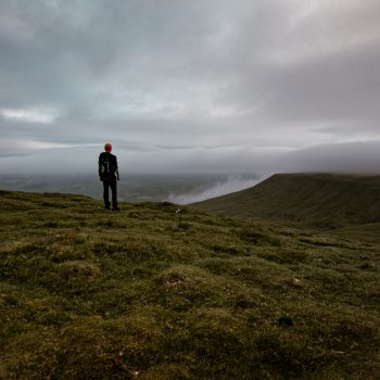 A person looking off into the summit view of Ingleborough in Yorkshire.