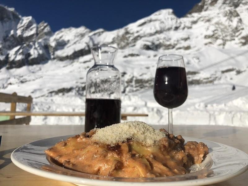 Italian pasta with a decanter of wine and a glass of red wine. There are snow capped mountains in the background.