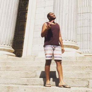 Justin in front of classic columns thinking about his opportunity to work remotely