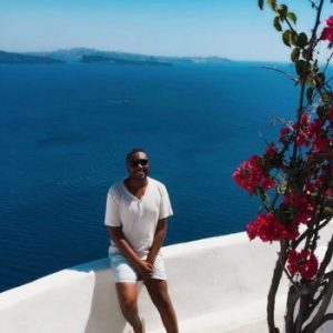 Justin sitting in front of the Mediterranean Sea before working remotely