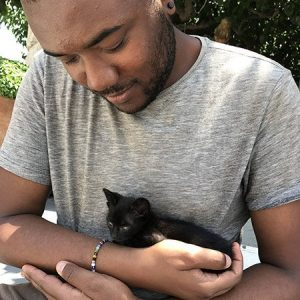 Justin holding a black kitten before working remotely.