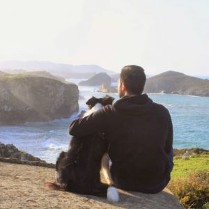 Marcos, hospitality professional, and his dog looking at the sea at Llanes in Asturias, Spain.