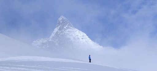 A view of the Matterhorn with a lone skier looking at the mountain peak.