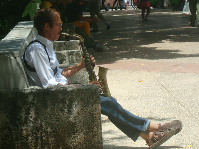 A photo of a street musician performing on a park bench.