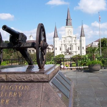 An image of a cannon and a historical building in New Orleans