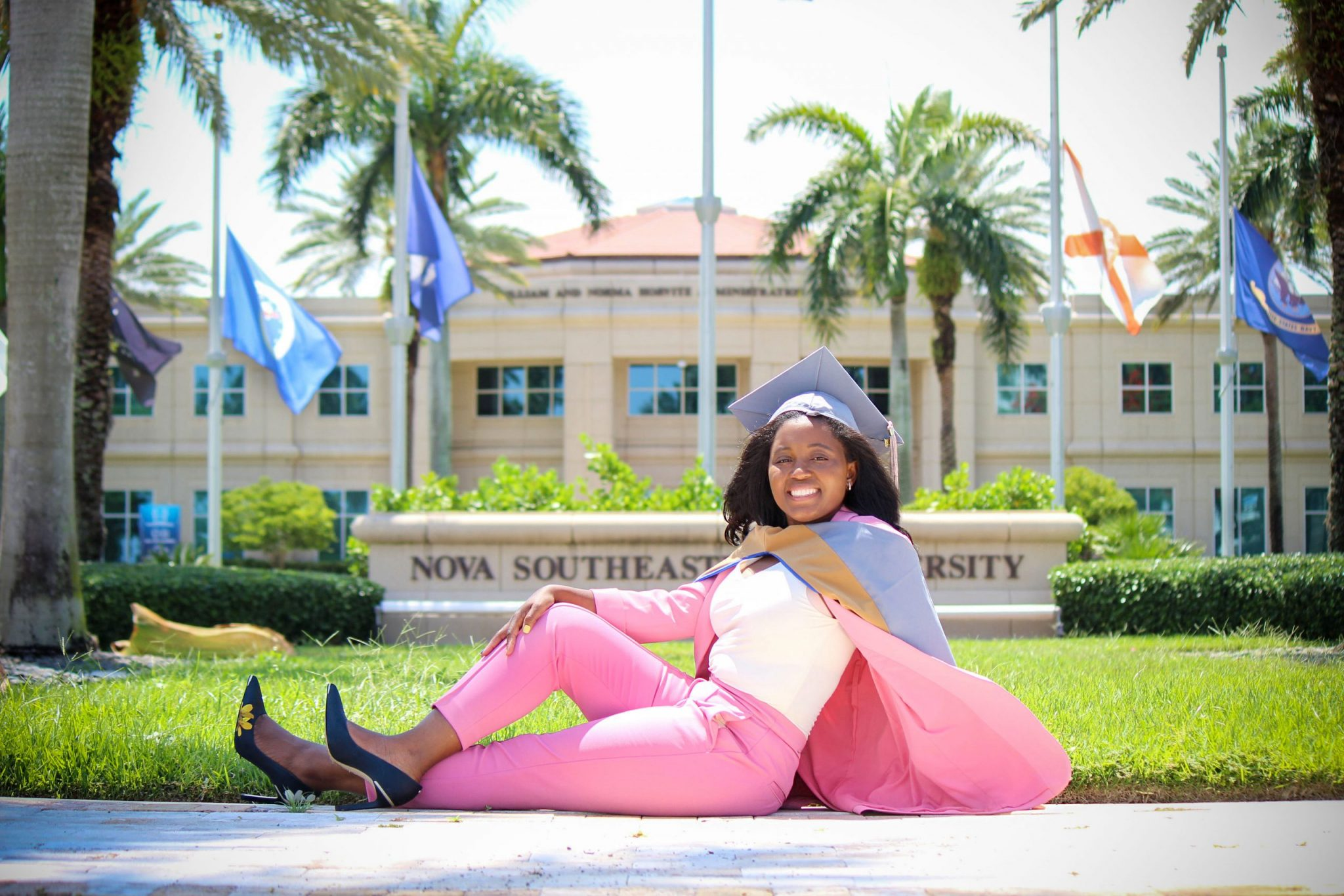 Paunise posing in front of the NOVA sign after earning her MBA