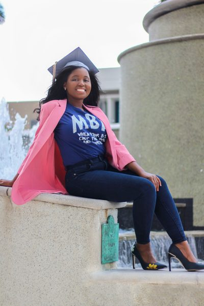 Paunise posing near a fountain after graduating with her MBA