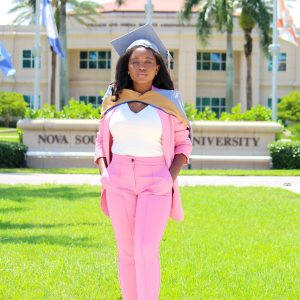 Paunise in front of the NOVA University sign after graduating with her MBA