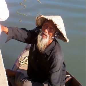 An older man in a boat wearing a rice hat.