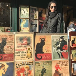 Leesa in front of a series of old fashioned posters abroad.
